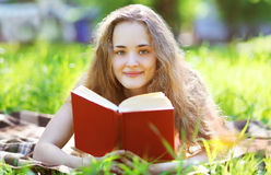 Muchacha feliz joven que lee un libro que miente en un parque Fotografía de archivo