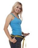 Muchacha feliz joven que mide su cintura Fotos de archivo