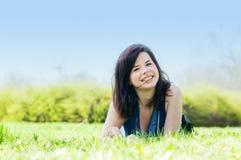 Muchacha feliz joven que miente en hierba Foto de archivo libre de regalías