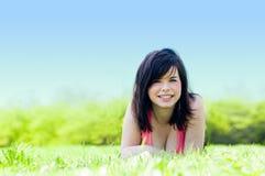 Muchacha feliz joven que miente en hierba Imagenes de archivo