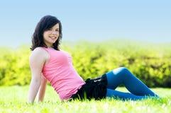 Muchacha feliz joven que miente en hierba Foto de archivo