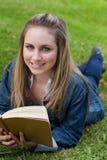Muchacha feliz joven que miente en la hierba mientras que sostiene un libro y un retrete Imagen de archivo