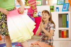 Muchacha feliz joven que mira la falda colorida imagenes de archivo