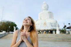 Muchacha feliz joven que se coloca con la estatua de Buda en Phuket, Tailandia Fotos de archivo
