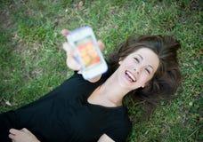 Muchacha feliz joven que se ríe del teléfono Fotografía de archivo