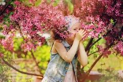 Muchacha feliz linda del niño en chaleco de los vaqueros que goza del manzano floreciente cercano de cangrejo de la primavera en  Fotografía de archivo libre de regalías