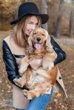 Muchacha feliz linda hermosa en un sombrero negro que juega con su perro Imágenes de archivo libres de regalías