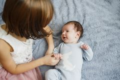 Muchacha feliz linda que detiene a su hermano recién nacido del bebé Fondo gris Bebé bonito en ropa azul imagen de archivo