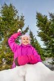 Muchacha feliz lista para lanzar la bola de nieve durante juego Fotografía de archivo libre de regalías