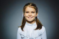 Muchacha feliz Niño hermoso del retrato del primer que sonríe en gris Fotografía de archivo libre de regalías