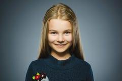 Muchacha feliz Niño hermoso del retrato del primer que sonríe en gris Foto de archivo libre de regalías