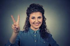 Muchacha feliz preciosa del retrato que muestra la victoria o el signo de la paz Fotos de archivo