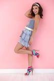 Muchacha feliz presentando en la mini alineada los altos talones Imagen de archivo libre de regalías