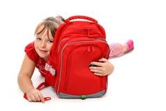 Muchacha feliz que abraza el bolso de escuela aislado en blanco Fotografía de archivo