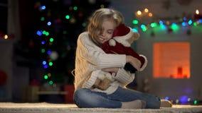 Muchacha feliz que abraza el oso de peluche en el traje de Papá Noel, creencia en hada-cuento de Navidad fotos de archivo libres de regalías