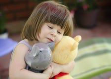 Muchacha feliz que abraza los juguetes Imagenes de archivo