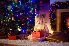 Muchacha feliz que abre el regalo mágico de la Navidad por una chimenea Imagen de archivo