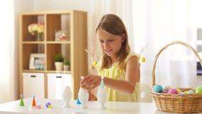 Muchacha feliz que adorna los huevos de Pascua en casa almacen de video