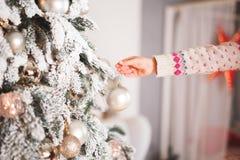 Muchacha feliz que adorna un árbol de navidad hermoso Imagen de archivo libre de regalías