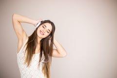 Muchacha feliz que baila y que escucha la música aislada Imagen de archivo libre de regalías
