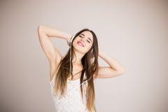 Muchacha feliz que baila y que escucha la música aislada Imagenes de archivo