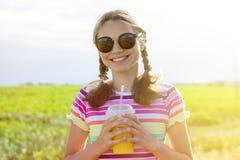 Muchacha feliz que bebe el zumo de naranja en el día de verano caliente Fotografía de archivo libre de regalías