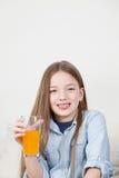 Muchacha feliz que bebe un jugo Fotografía de archivo libre de regalías