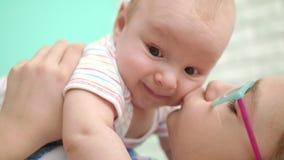 Muchacha feliz que besa al bebé Ciérrese para arriba de niño del abrazo de la muchacha almacen de video
