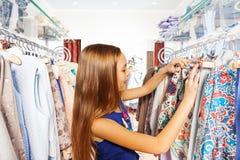 Muchacha feliz que busca para la ropa durante compras Foto de archivo libre de regalías