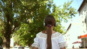 Muchacha feliz que camina abajo de la calle de la ciudad en auriculares y que escucha la música muchacha en un vestido blanco con metrajes