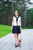 Muchacha feliz que camina con el terrier de Yorkshire del perro Imágenes de archivo libres de regalías