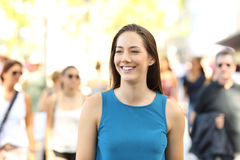 Muchacha feliz que camina entre otras personas Imágenes de archivo libres de regalías