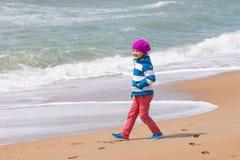 Muchacha feliz que camina a lo largo de la playa costera del mar en día de primavera caliente Foto de archivo libre de regalías