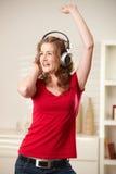 Muchacha feliz que canta con los auriculares Foto de archivo