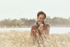 Muchacha feliz que celebra los teléfonos móviles en los prados en la guerra foto de archivo libre de regalías