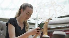 Muchacha feliz que charla en línea en café almacen de metraje de vídeo