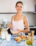 Muchacha feliz que cocina la tortilla con leche Foto de archivo libre de regalías