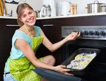 Muchacha feliz que cocina pescados en horno Fotografía de archivo