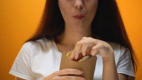 Muchacha feliz que come las patatas fritas, los sabores artificiales y el gusto aumentado, apego metrajes