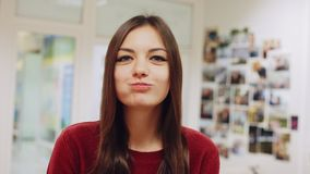 Muchacha feliz que come un buñuelo, gozando de un bocado en el trabajo almacen de metraje de vídeo