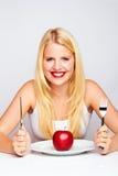 Muchacha feliz que come una manzana roja Fotos de archivo libres de regalías