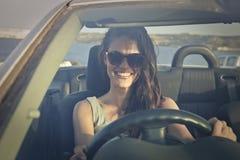Muchacha feliz que conduce un coche Fotografía de archivo