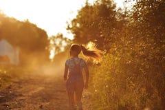 Muchacha feliz que corre abajo de una carretera nacional Imagen de archivo libre de regalías