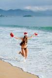 Muchacha feliz que corre con el regalo de los chrismas en la playa Imágenes de archivo libres de regalías