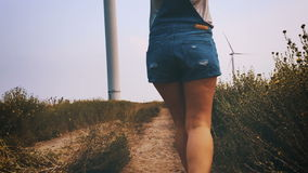 Muchacha feliz que corre hacia la turbina de viento, cámara lenta almacen de video