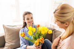 Muchacha feliz que da las flores para mimar en casa Imagen de archivo libre de regalías