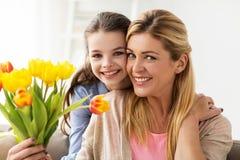 Muchacha feliz que da las flores para mimar en casa Fotos de archivo libres de regalías