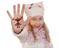 Muchacha feliz que demuestra el símbolo de la Navidad pintado en su mano Reno Fotografía de archivo