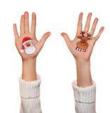 Muchacha feliz que demuestra los símbolos de la Navidad pintados en las manos Papá Noel y reno Fotografía de archivo libre de regalías