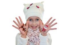 Muchacha feliz que demuestra los símbolos de la Navidad pintados en las manos Papá Noel y reno Imagen de archivo libre de regalías